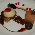 Panacota com molho de frutas vermelhas, pera ao vinho, noz folhada e chocolate trufado